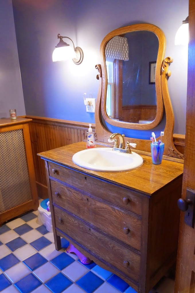 Old fashioned bathroom with tile and dresser turned vanity